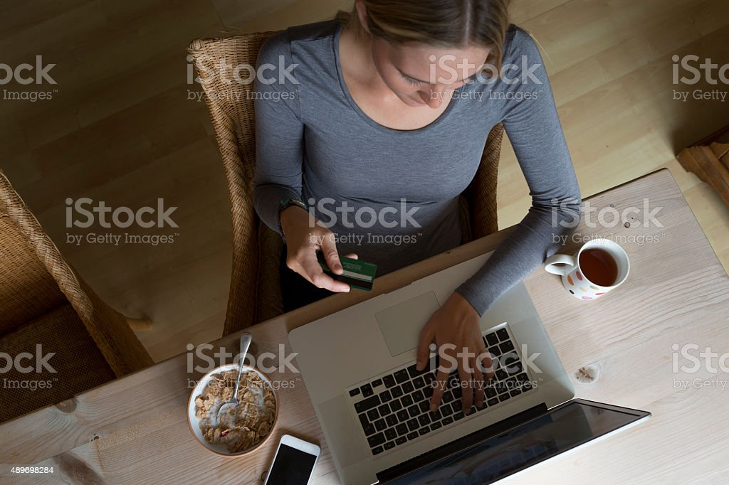 Woman using laptop to make a card payment stock photo