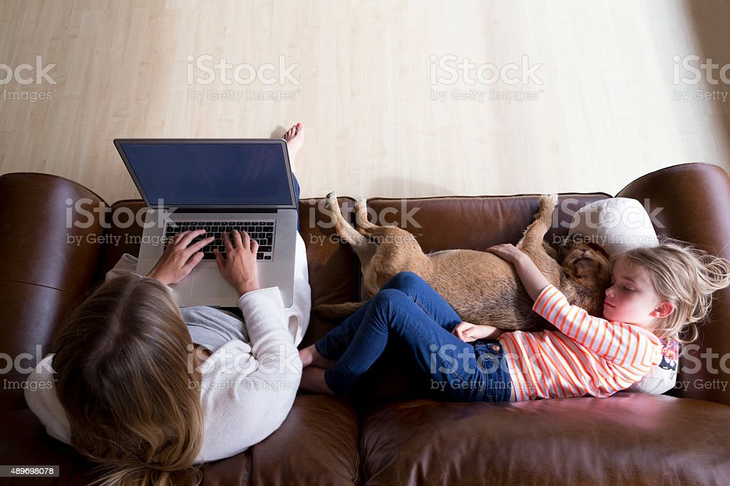 woman using laptop while daughter and dog sleep stock photo