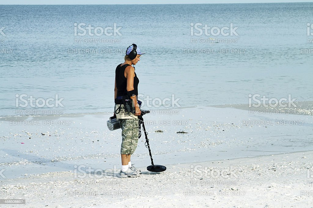 Woman using metal detector on beach, Marco Island, Florida stock photo