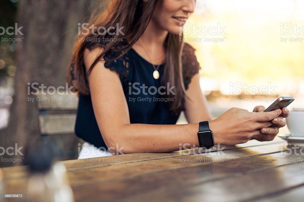 Woman using mobile phone at cafe stock photo