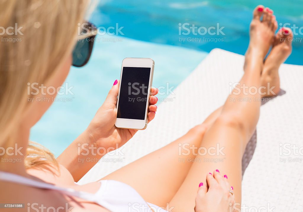 Woman using mobile phone by the pool stock photo