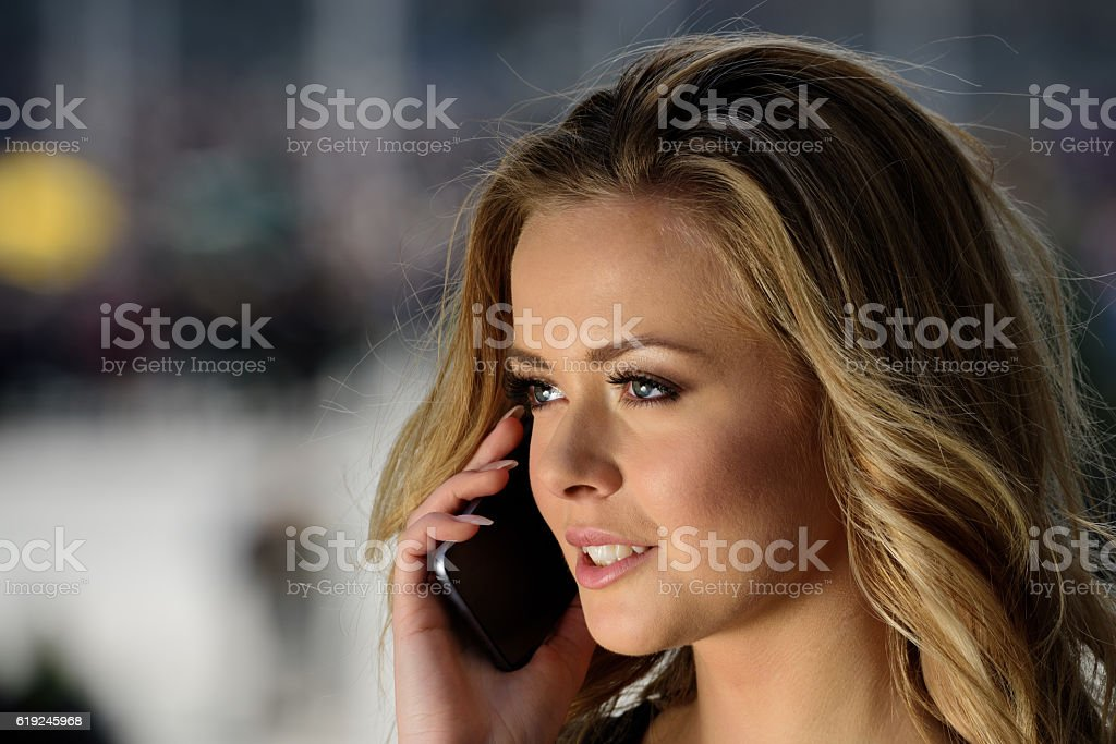 Woman using mobile phone in city sunset stock photo