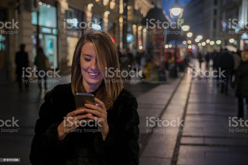 Woman using Mobile Phone in the street, night light bokeh stock photo
