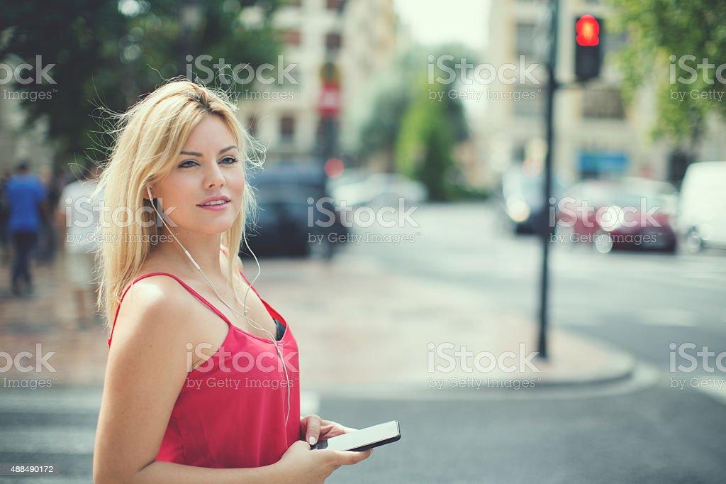 Woman using mobile phone in urban settings stock photo
