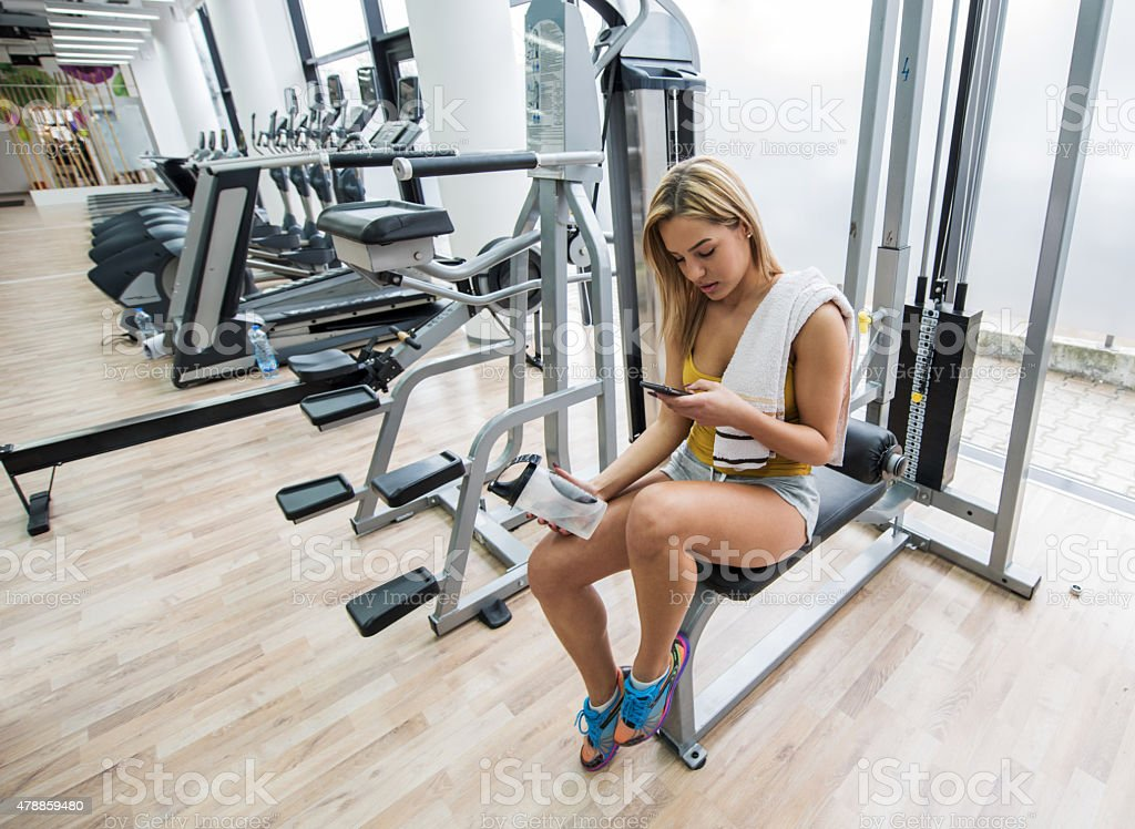 Woman using mobile phone on a break at gym. stock photo