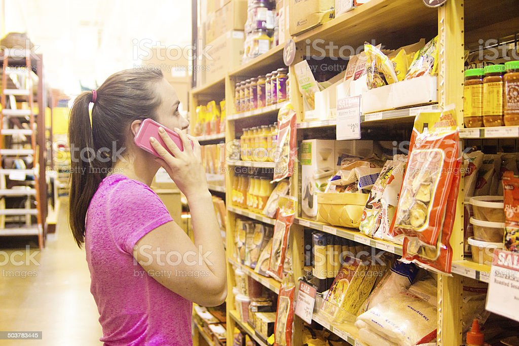 Woman Using Mobile Phone While Shopping in Grocery Market stock photo