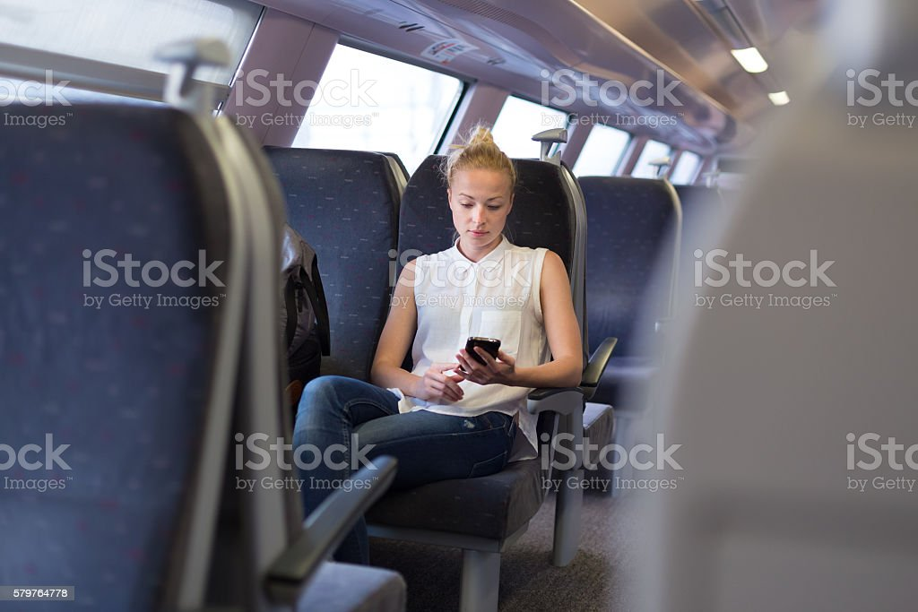Woman using mobile phone while travelling by train. stock photo