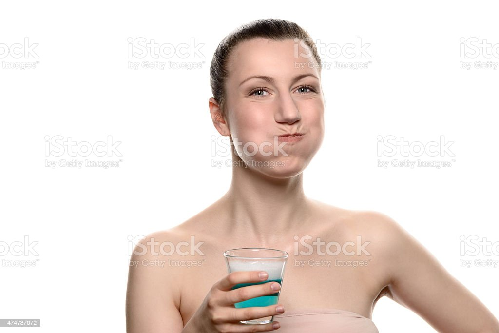 Woman using mouthwash during oral hygiene routine stock photo