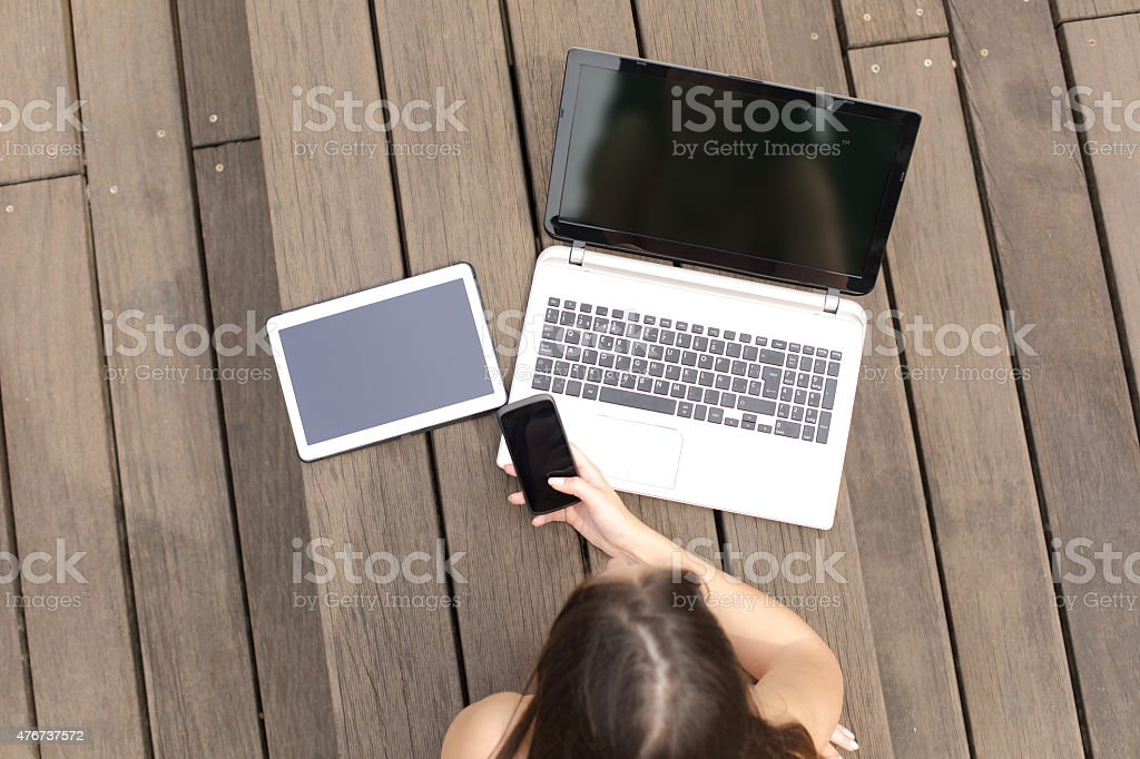 Woman using multiple devices phone laptop and tablet stock photo