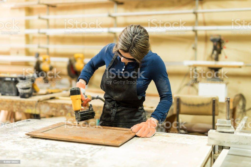 Woman using nail gun in a woodshop stock photo