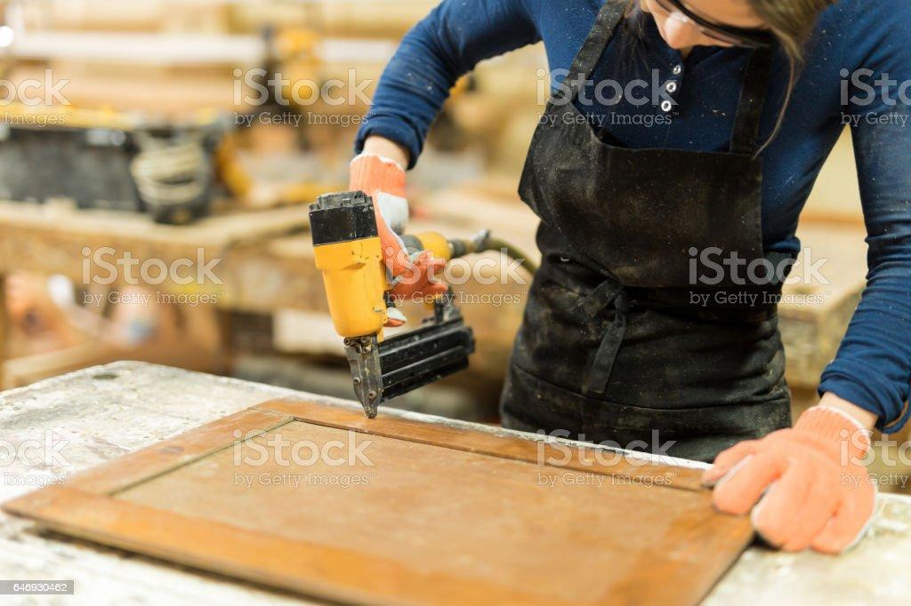 Woman using nail gun on some wood stock photo