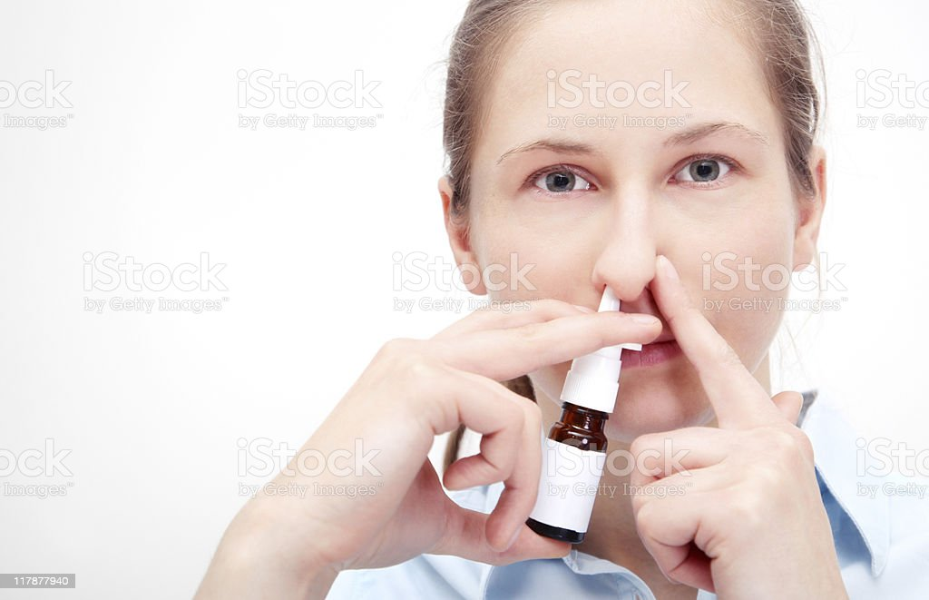 Woman using nasal spray and holding other nostril closed. royalty-free stock photo