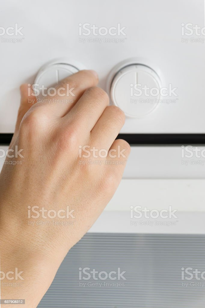 Woman Using Oven Controls stock photo