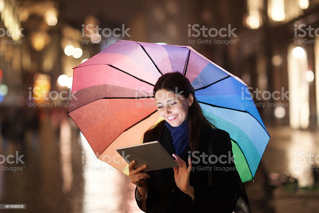 Woman using pad under umbrella in the evening city stock photo