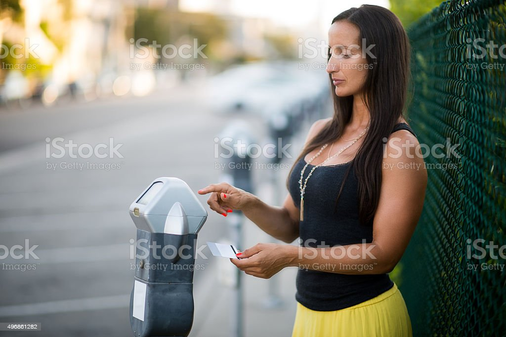 Woman using parking meter stock photo