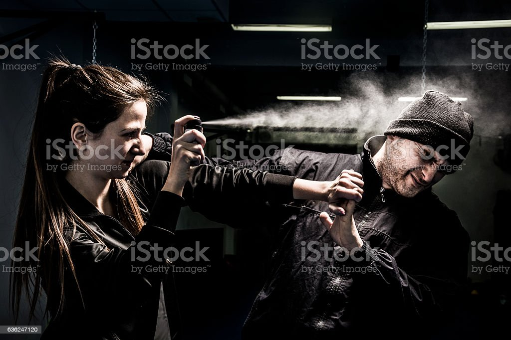 Woman using pepper spray for self defense against attacker stock photo