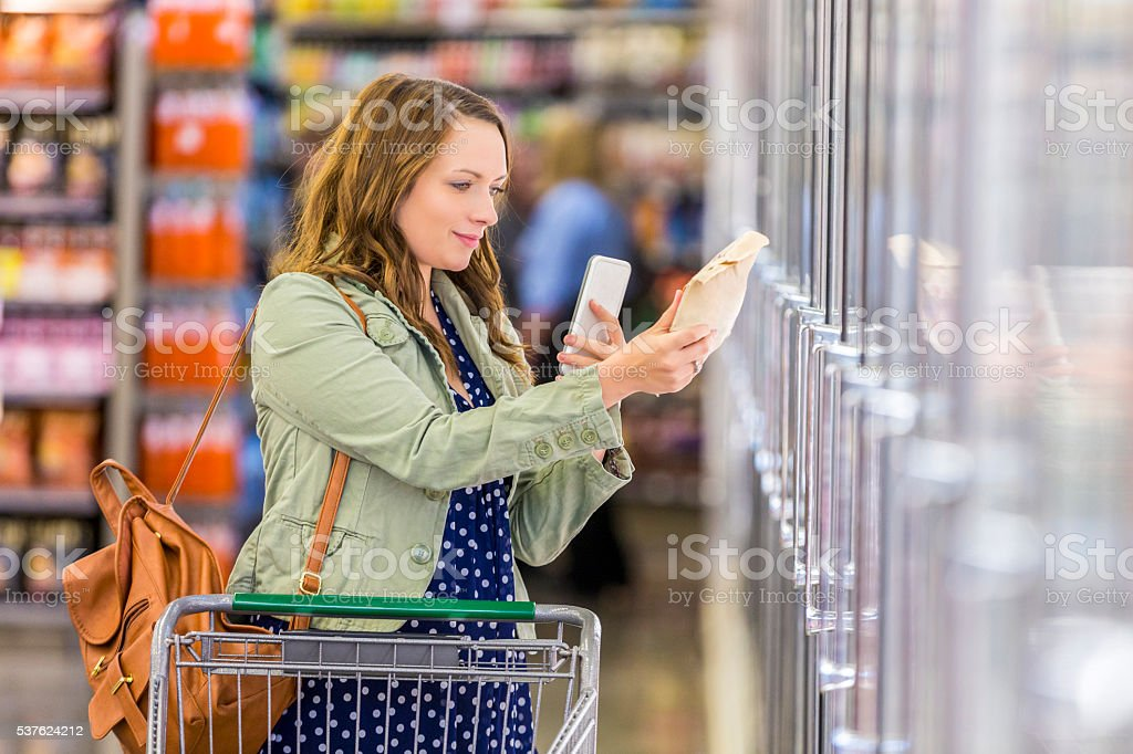 Woman using phone at grocery store stock photo