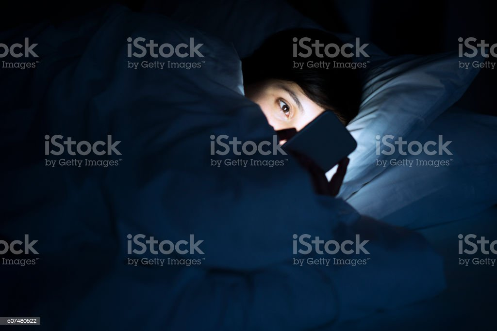 Woman using phone in bed stock photo