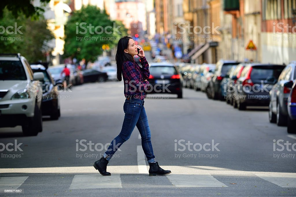 Woman using phone Stockholm city street in background stock photo
