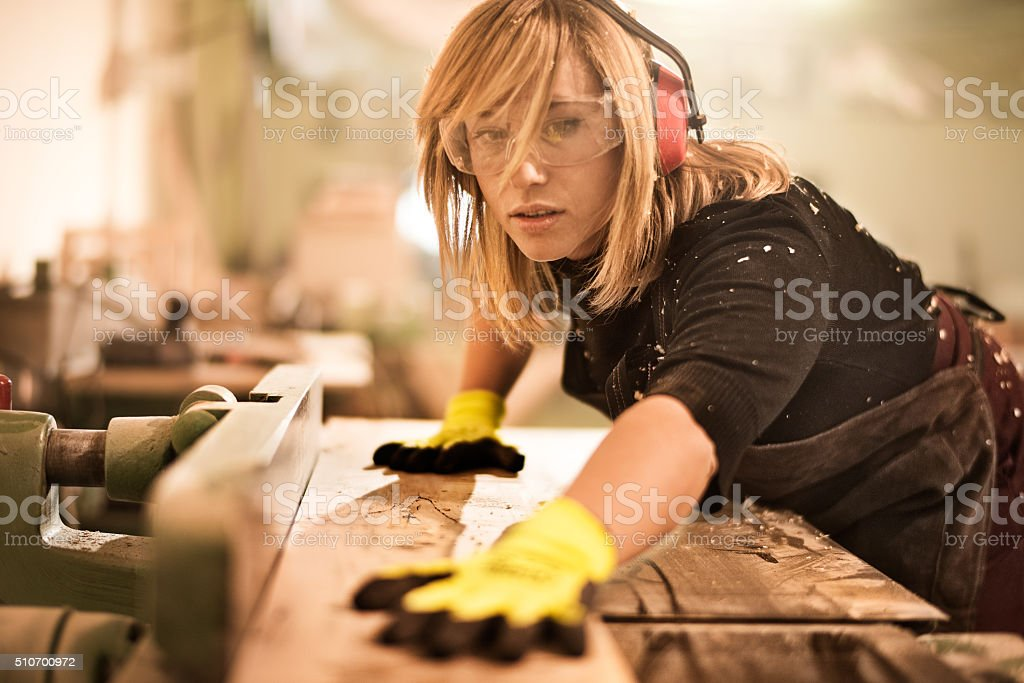 Woman using plank cutter stock photo