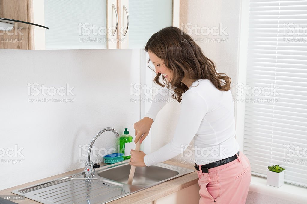 Woman Using Plunger In Sink stock photo