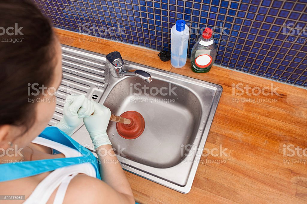 Woman Using Plunger stock photo