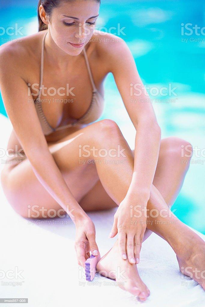 Woman using pummis stone royalty-free stock photo