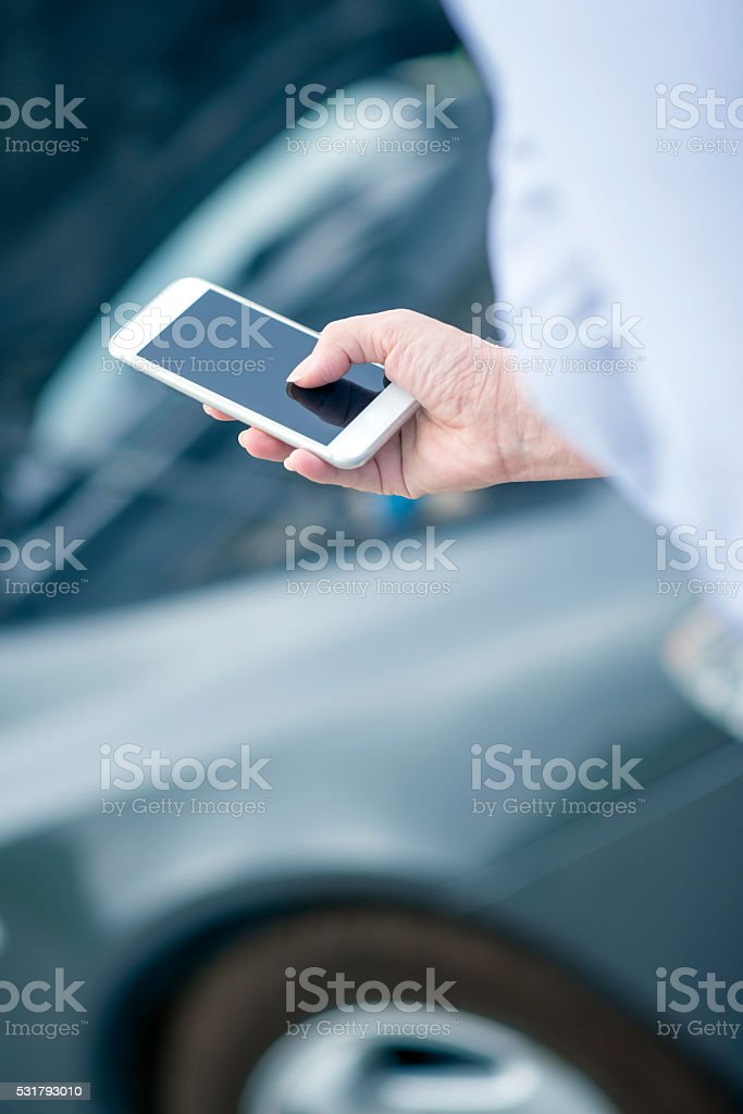 Woman using smart phone and call the car insurance stock photo