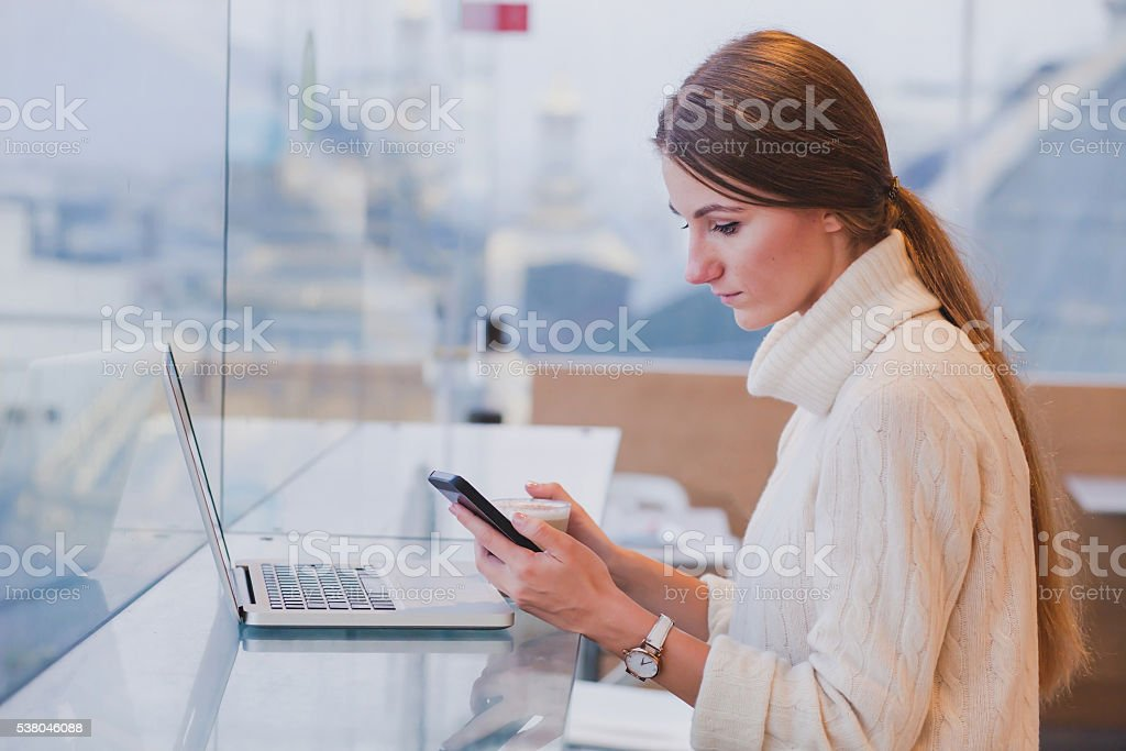 woman using smart phone in modern cafe stock photo