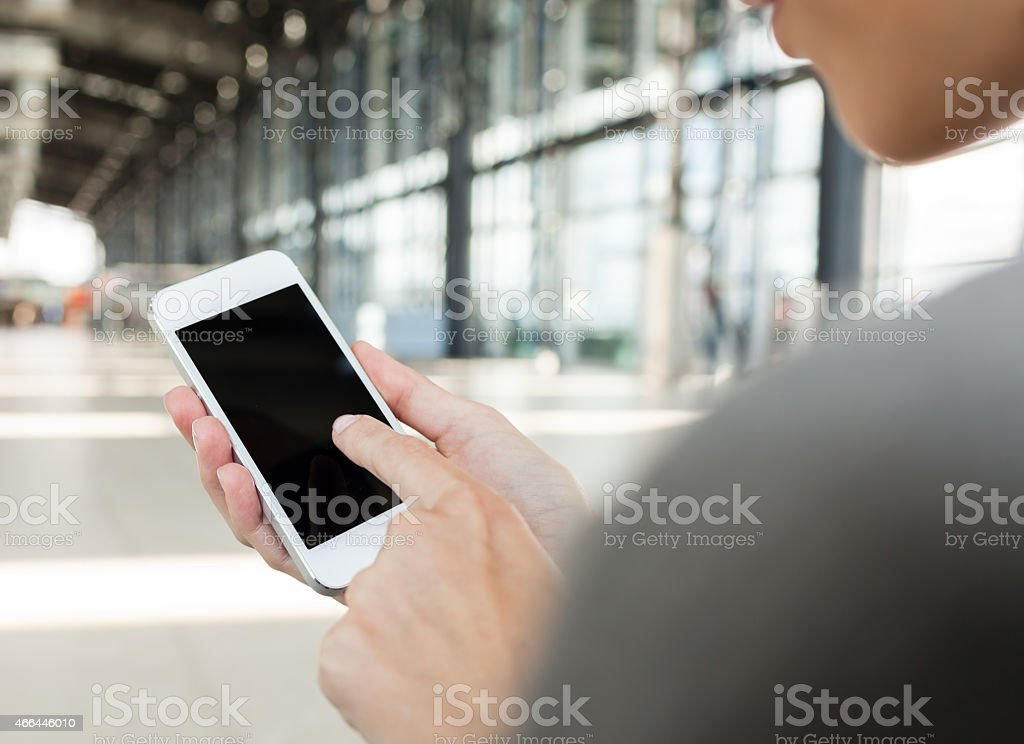 Woman using smart phone in the airport stock photo