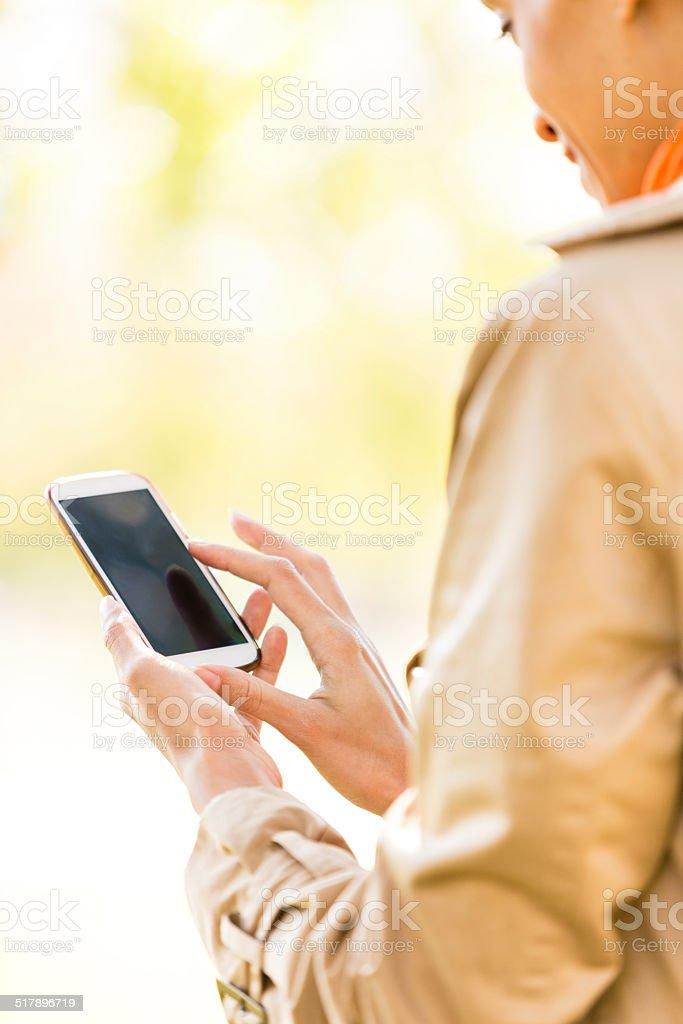 Woman using smart phone outdoors stock photo
