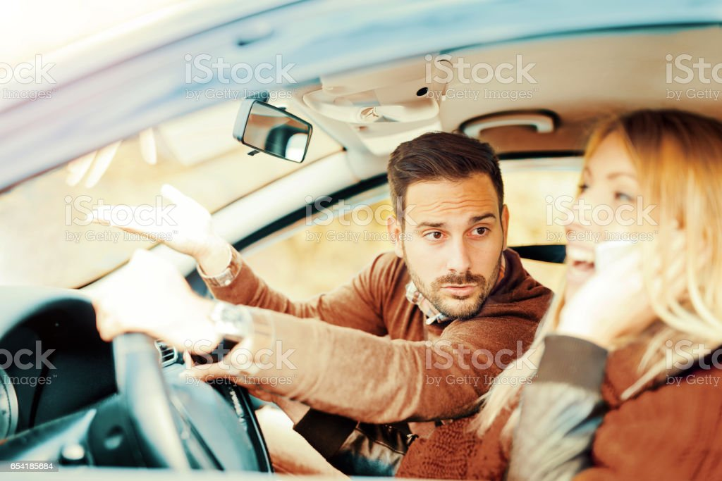 Woman using smart phone while driving a car. Dangerous driving stock photo