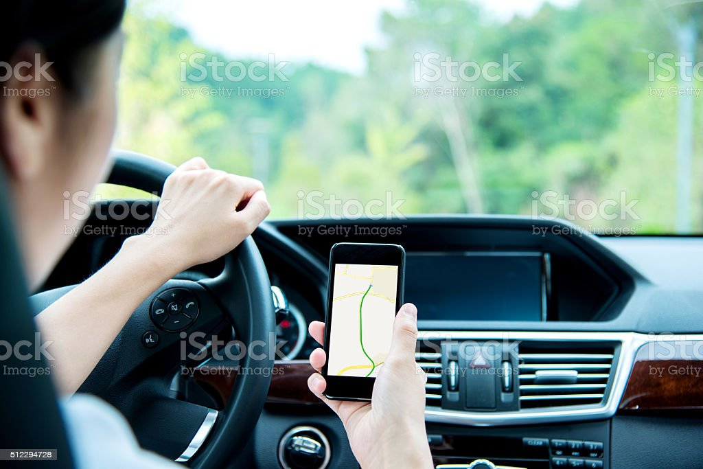Woman using smart phone while driving stock photo