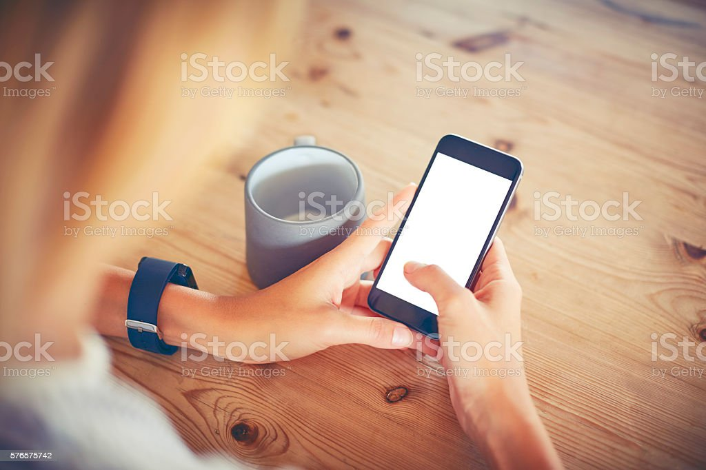 Woman using smart phone with blank screen at table stock photo