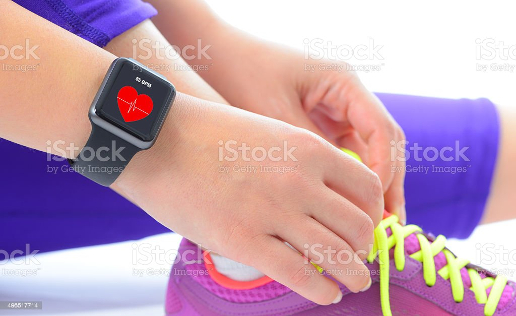 Woman using smart watch with heart rate monitor stock photo