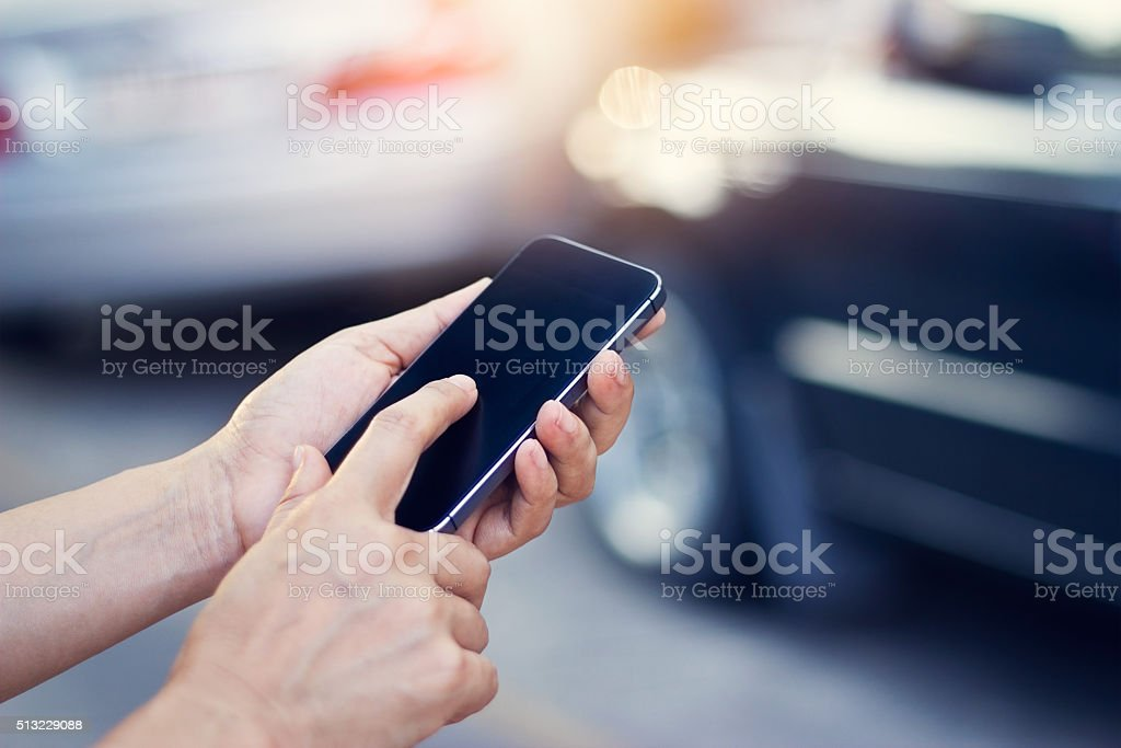 woman using smartphone at roadside after traffic accident stock photo