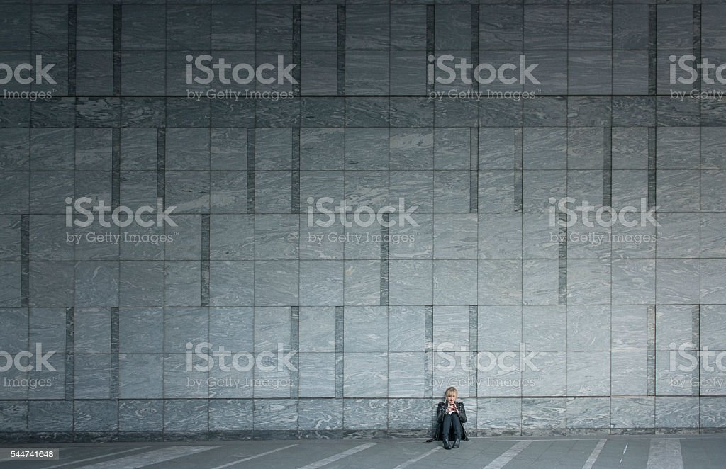 Woman using smartphone by large wall. stock photo