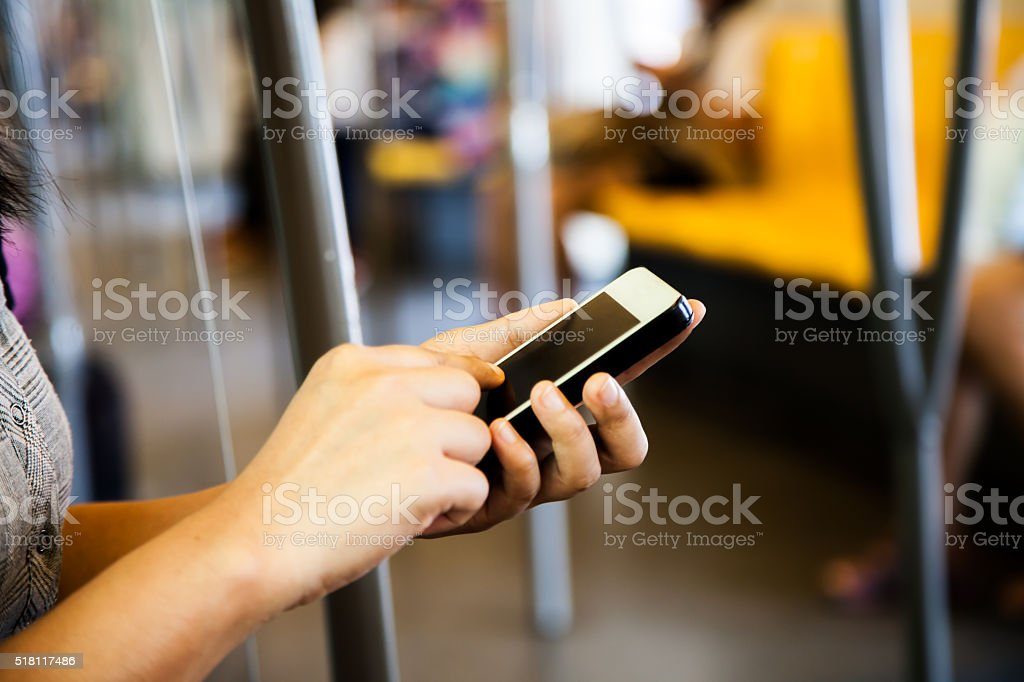 Woman using smartphone, cellphone in subway stock photo