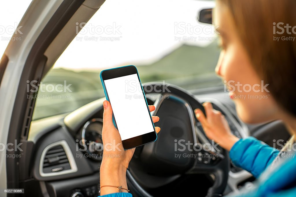 Woman using smartphone driving the car stock photo