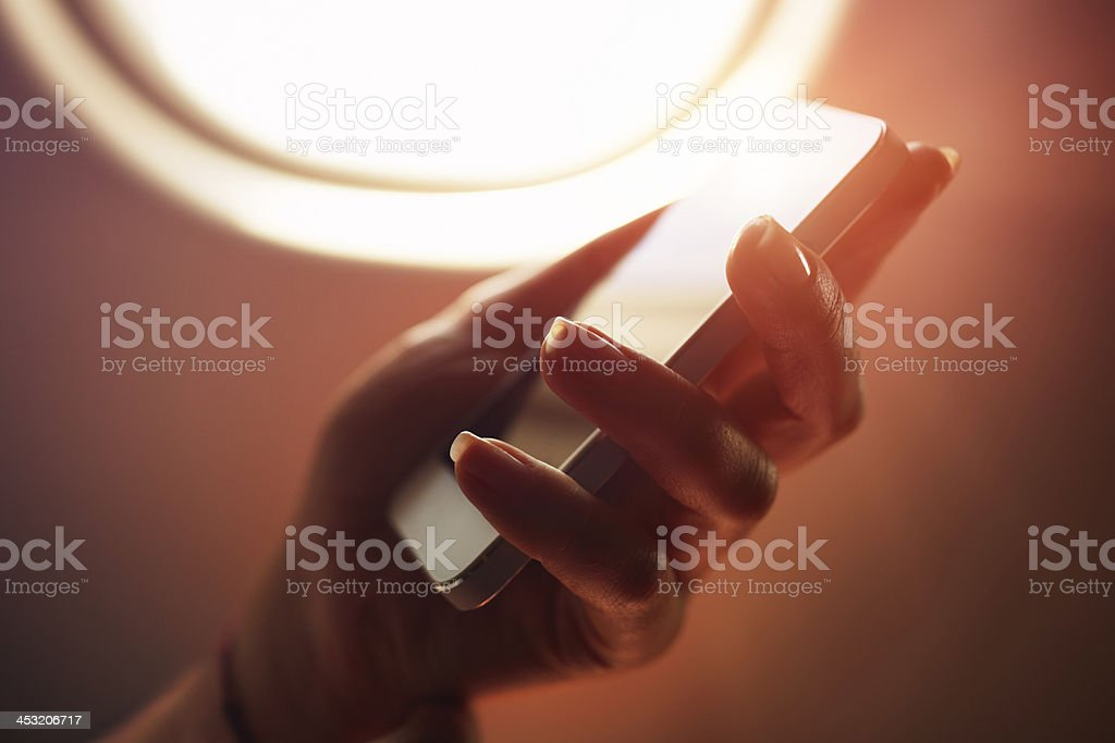 Woman using smartphone in airplane during flight royalty-free stock photo
