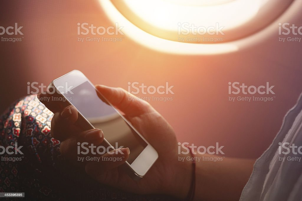 Woman using smartphone in airplane during flight stock photo