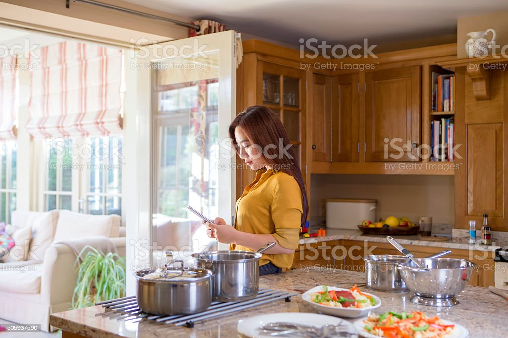 Woman Using Smartphone in Kitchen stock photo