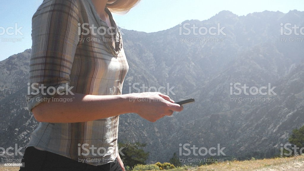 Woman using smartphone in mountain range stock photo