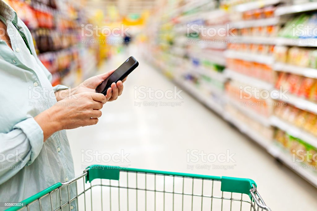 Woman using smartphone in supermarket stock photo