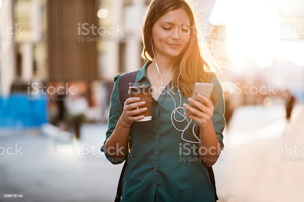 Woman using smartphone in the street stock photo