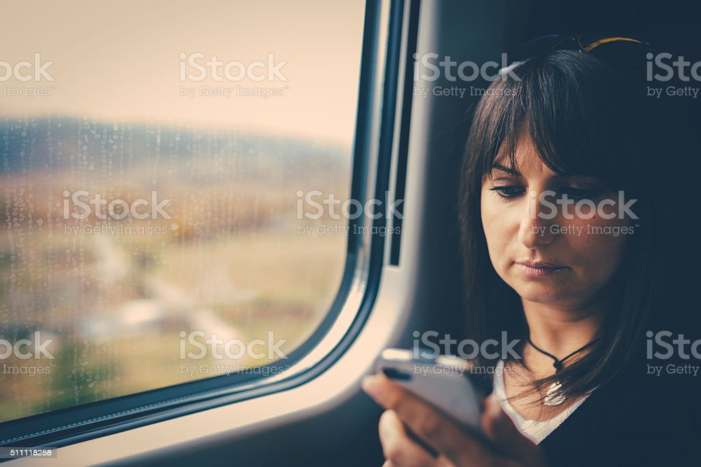 Woman using smartphone in train stock photo