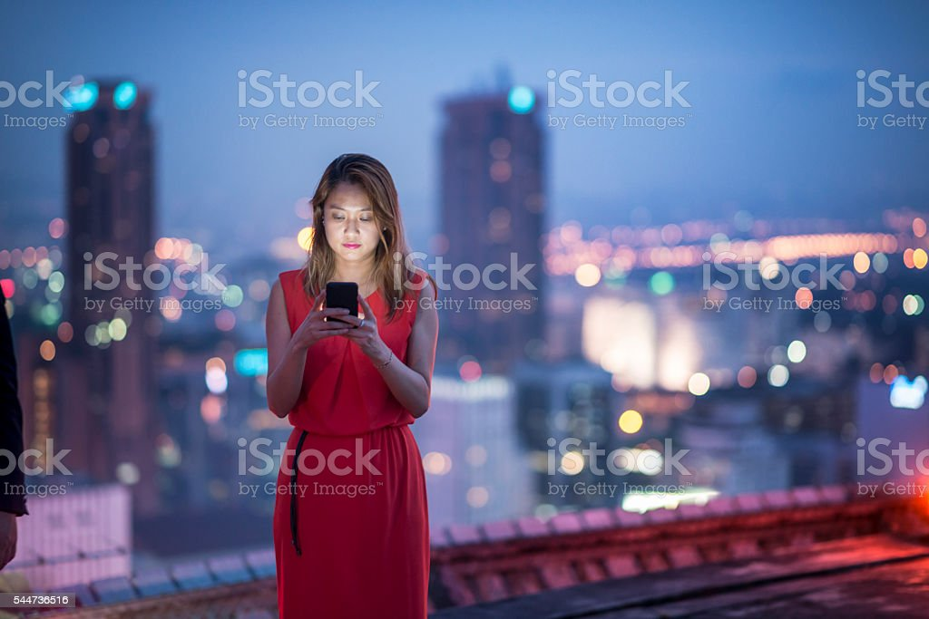 Woman using smartphone on rooftop. stock photo