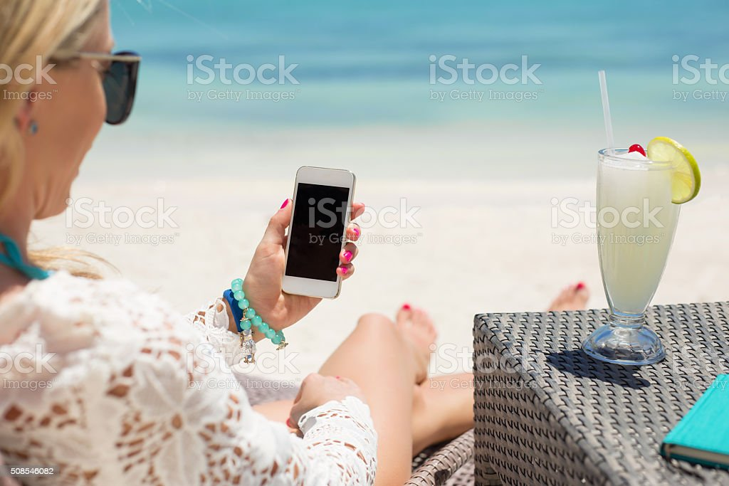 Woman using smartphone on the beach stock photo