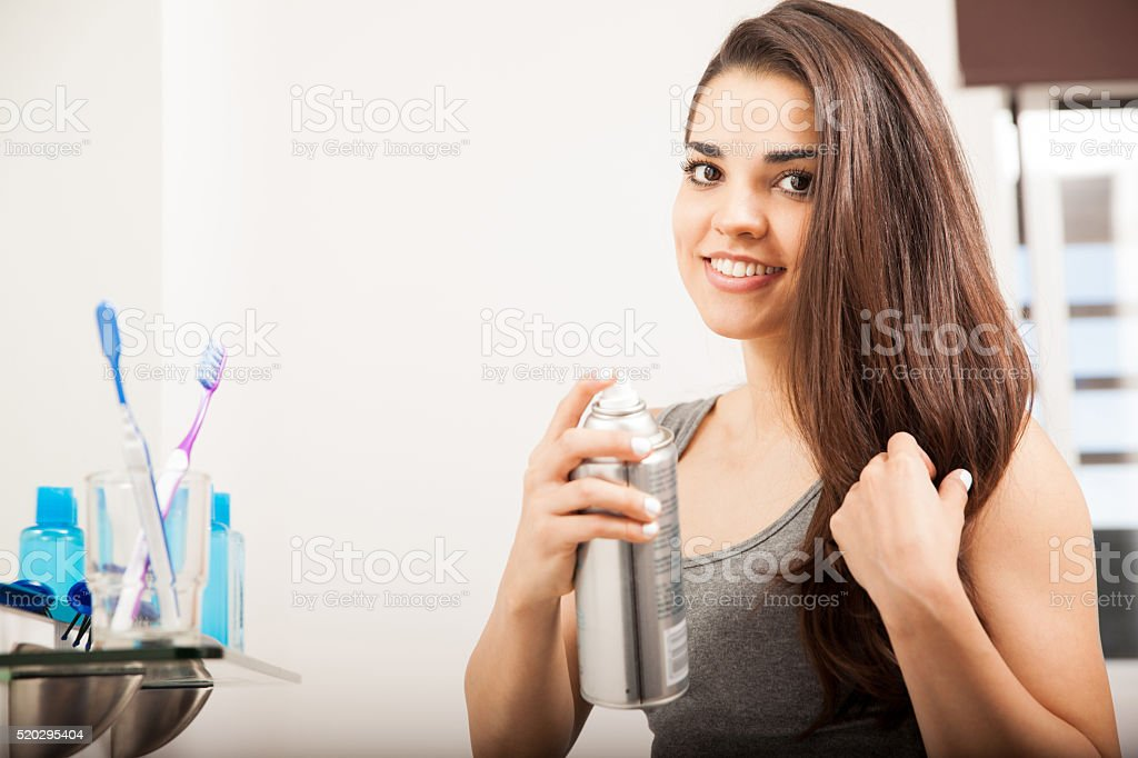 Woman using some spray to style her hair stock photo