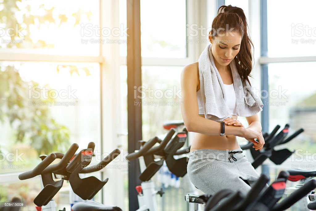 woman using sport bracelet during spinning stock photo